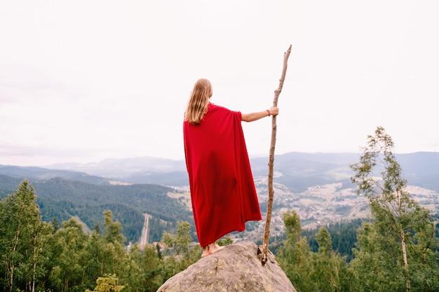 Mulher desconhecida na capa vermelha em pé na pedra no topo da montanha