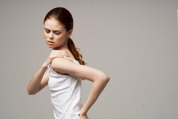 Mulher descontente com dor no braço, artrite, doença crônica, luz de fundo