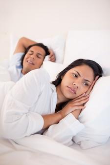 Mulher descontente deitada ao lado do namorado ronco