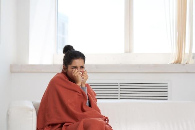 Mulher descontente e deitada em casa no sofá para resfriados