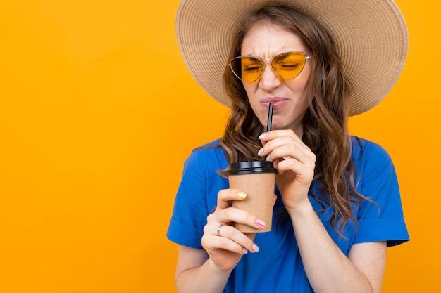 Mulher descontente em um chapéu de palha e óculos bebe café sem gosto