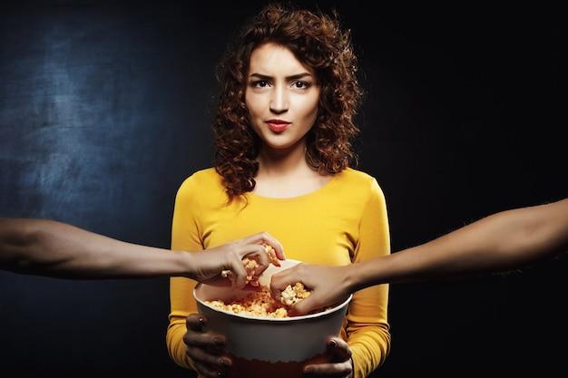 Mulher descontente segurando balde de pipoca nas mãos olhando direto