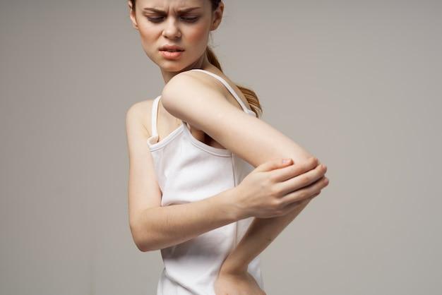 Mulher descontente segurando o cotovelo problemas de saúde tratamento conjunto de tratamento em estúdio