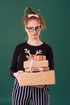 Mulher descontente segurando uma pilha de presente de natal