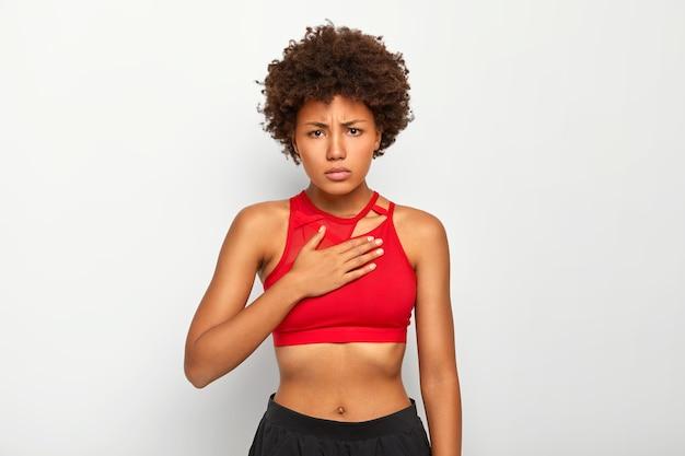 Mulher descontente sente dores agudas no peito, respira com dificuldade, usa roupas esportivas, parece chateada, tem cabelo afro