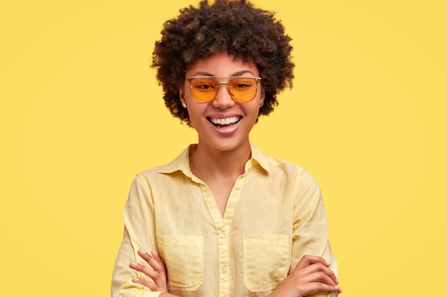 Mulher descontraída com sorriso largo, penteado afro, fica com as mãos cruzadas, usa tons da moda