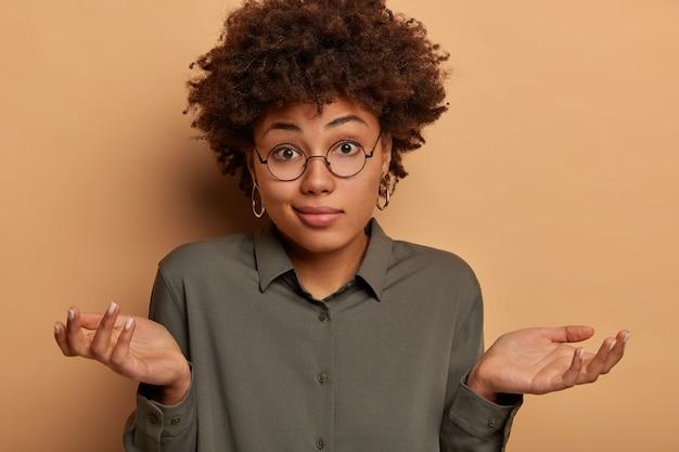 Mulher descuidada e hesitante encolhe os ombros, abre os braços para os lados, não consegue ajudar ou tem dúvidas, usa uma camisa estilosa e óculos grandes