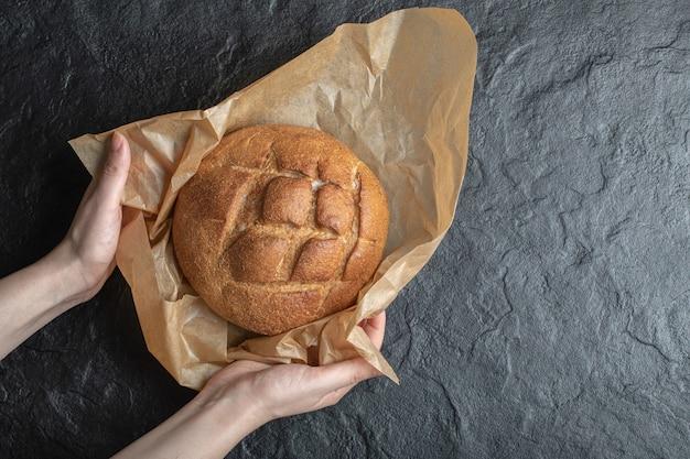 Mulher desembrulhar pão de centeio acabado de fazer em fundo preto.