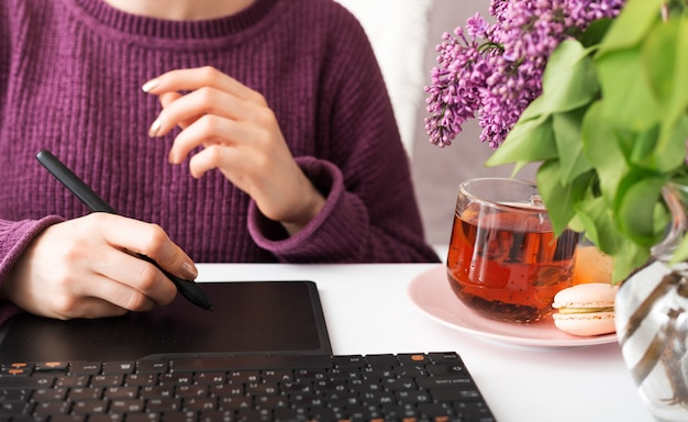 Mulher desenha na mesa digitalizadora. o designer freelancer retoucher de designer gráfico trabalha em casa. trabalho remoto no aconchegante escritório em casa
