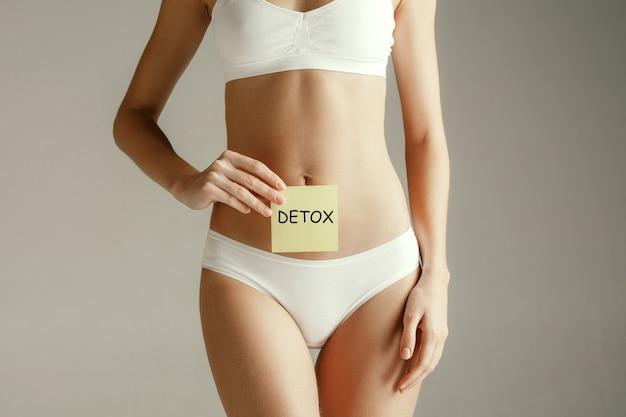 Mulher desenhando a palavra detox em nota adesiva