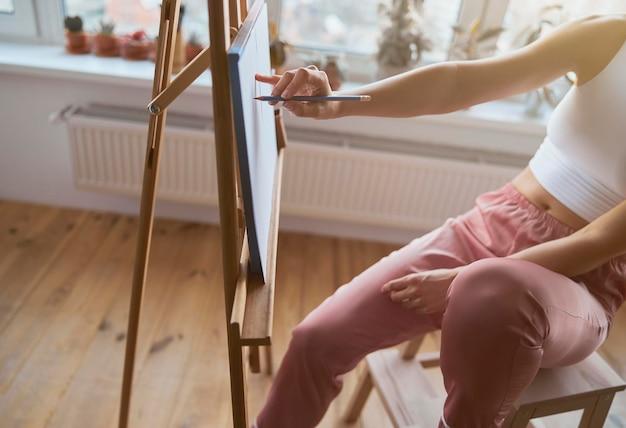Mulher desenhando na tela com lápis de grafite na varanda iluminada