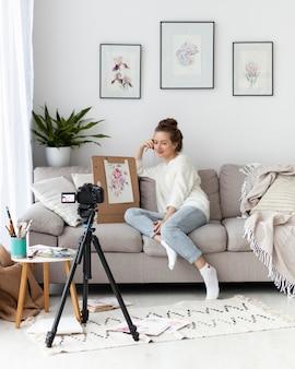 Mulher desenhando para um tutorial online dentro de casa