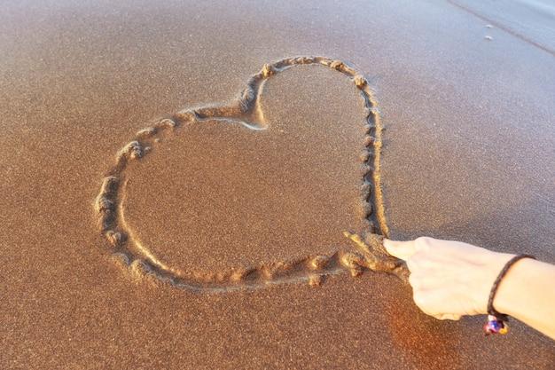 Mulher desenhando um coração na areia ao pôr do sol em um conceito de amor de verão.