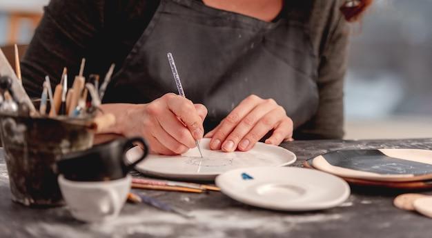 Mulher desenhando um padrão criativo em um prato feito na oficina de cerâmica