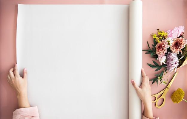 Mulher desenrola um papel em uma mesa rosa ao lado de um buquê de flores