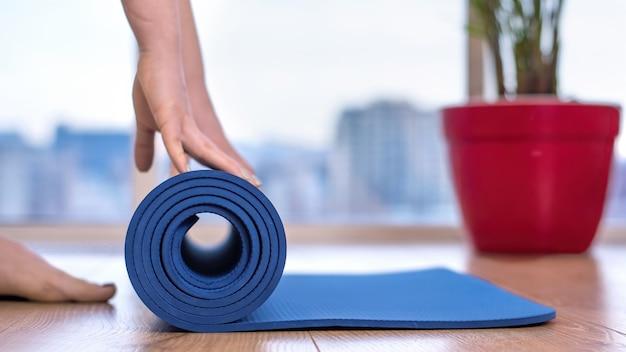 Mulher desenrolando um tapete de ioga azul para treinar em casa