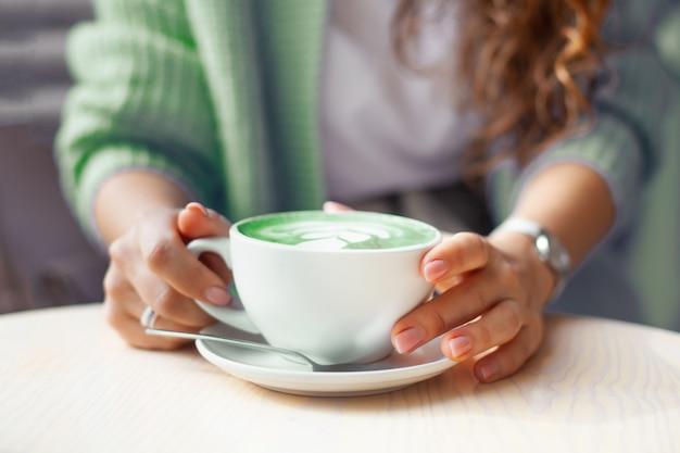 Mulher desfocada com as mãos segurando uma xícara de ervilha com leite quente ou espirulina com leite azul na mesa de madeira. bebida orgânica saudável e moderna. conceito de bem-estar e desintoxicação. copie o espaço.