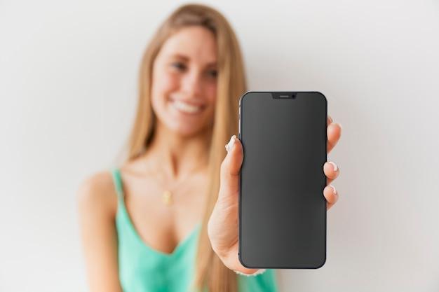 Mulher desfocada de frente mostrando seu smartphone com tela vazia