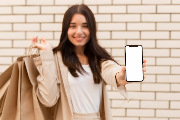 Mulher desfocada mostrando cópia de telefone celular