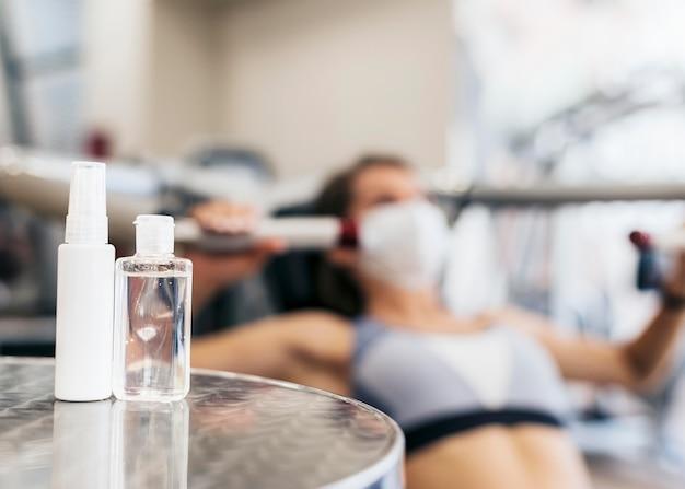 Mulher desfocada na academia usando equipamento com máscara médica e frasco de desinfetante para as mãos
