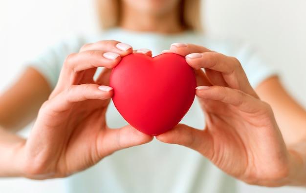 Mulher desfocada segurando formato de coração