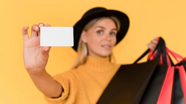 Mulher desfocada segurando um cartão de espaço de cópia e sacolas de compras