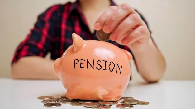 Mulher desfocada, vestindo uma camisa quadriculada da moda, joga moedas no cofrinho com inscrição de pensão, coletando dinheiro para medicamentos.