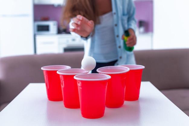 Mulher desfrutando de jogo de pong de cerveja na mesa em casa