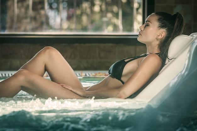 Mulher desfrutando de procedimento de spa na piscina