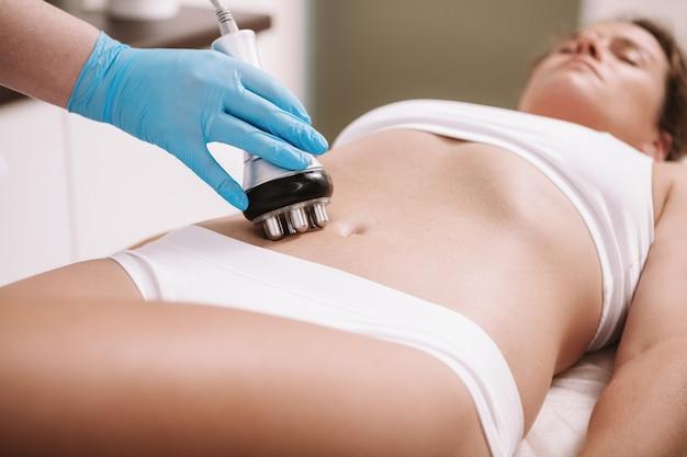 Mulher, desfrutando de rf-lifting procedimento na pele do estômago na clínica de beleza