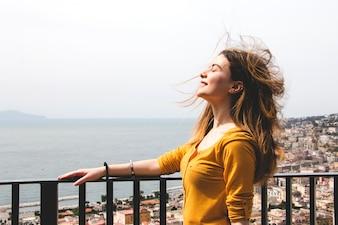 Mulher desfrutando de sopro de vento