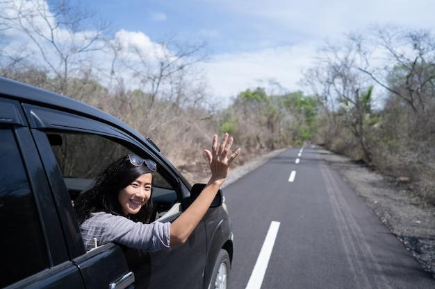 Mulher, desfrutando de sua viagem de férias de carro