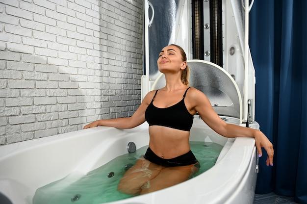 Mulher desfrutando de terapia de hidromassagem em uma banheira em cápsula de spa para tratamento não invasivo anti-envelhecimento e anticelulite em centro de spa de bem-estar