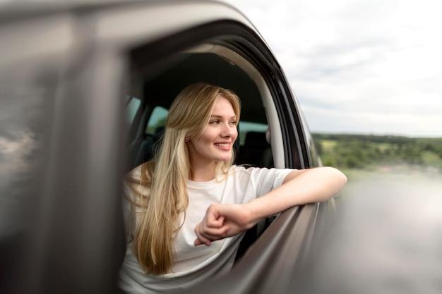 Mulher desfrutando de um passeio de carro