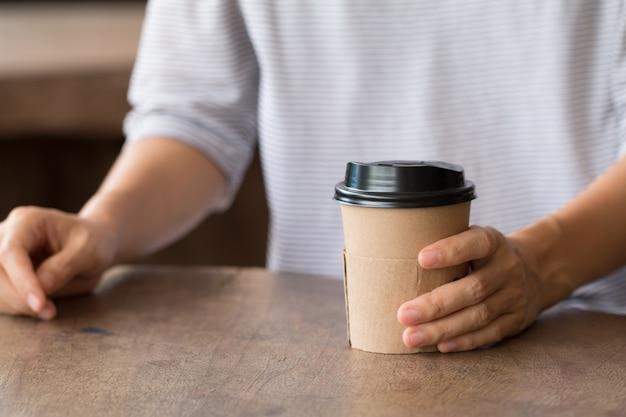 Mulher desfrutando de uma bebida quente, café tardio em copo de papel