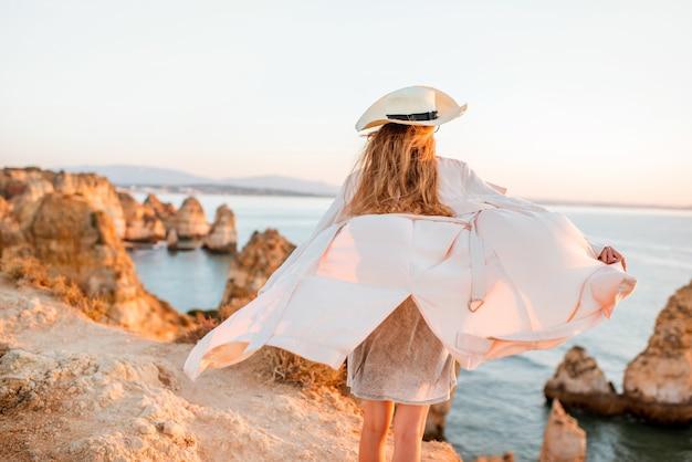 Mulher desfrutando de uma bela vista da costa rochosa durante o nascer do sol em lagos, no sul de portugal