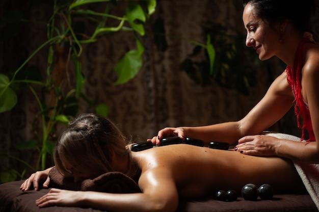 Mulher desfrutando relaxante massagem nas costas no centro de spa de cosmetologia.