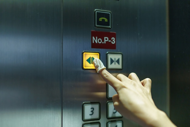 Mulher, desgastar, borracha, dedo, apertar um botão, elevador