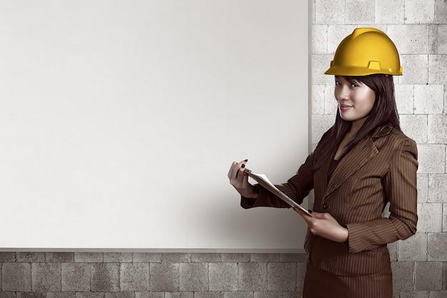 Mulher, desgastar, capacete, segurando clipboard