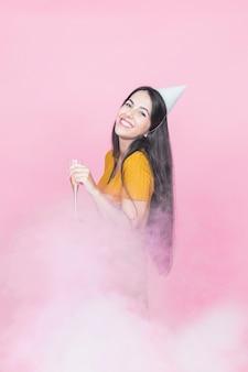 Mulher, desgastar, chapéu partido, segurando, flauta champanha, ficar, fumaça, contra, fundo cor-de-rosa