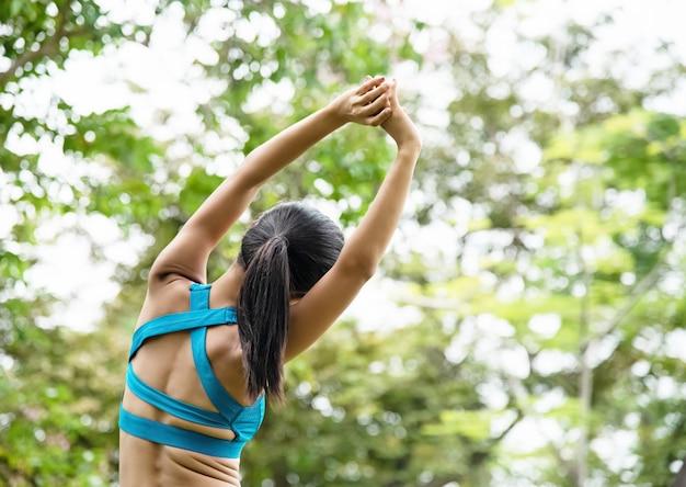 Mulher, desgastar, exercício, paleto, esticar, costas, e, corpo, levantar, mãos cima, e, alcance, ar