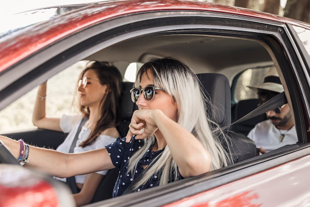 Mulher, desgastar, óculos de sol, dirigindo carro, com, dela, amigos