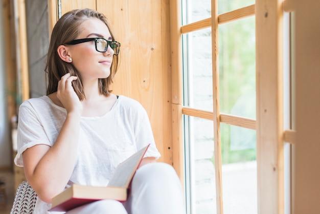 Mulher, desgastar, óculos, olhar através janela