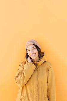 Mulher, desgastar, tricotado, chapéu, olhar, câmera, ficar, contra, fundo amarelo