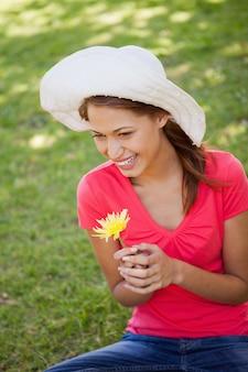 Mulher, desgastar, um, chapéu branco, enquanto, segurando, um, flor amarela