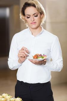 Mulher desgostoso com petiscos exóticos na mesa de buffet