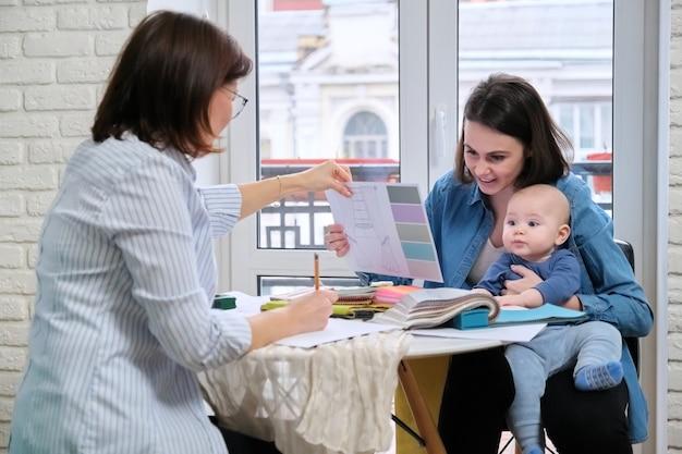 Mulher designer de interiores e cliente com bebê escolhendo tecidos e materiais.