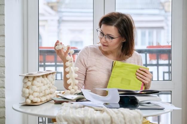 Mulher designer de interiores trabalhando à mesa de um escritório com amostras de tecidos decorativos de interiores para cortinas, estofados, acessórios