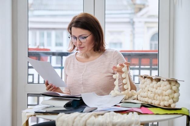 Mulher designer de interiores trabalhando na mesa de um escritório com amostras de tecidos decorativos de interiores para cortinas, estofados, acessórios