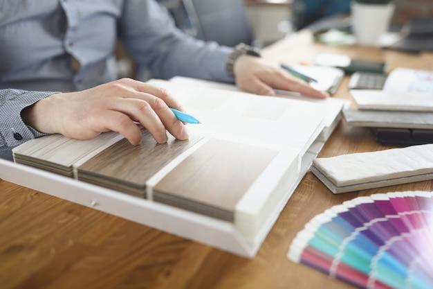 Mulher designer folheando o catálogo com amostras de laminado de madeira closeup